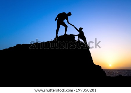 Teamwork couple hiking help each other trust assistance silhouette in mountains, sunset. Teamwork Male and woman hiker helping each other on top of mountain climbing team, beautiful sunset landscape. - stock photo