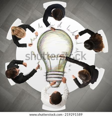 Teamwork draws a big idea during a meeting - stock photo
