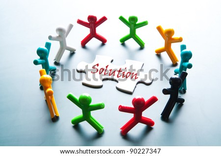 Teamwork for solve problem. Plastic doll group work with puzzle. - stock photo