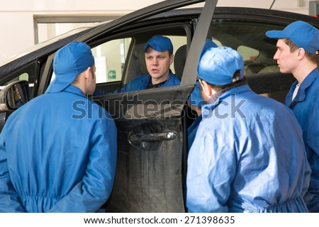 Teamwork: Group of Engineers and Mechanics People during Vehicle Repairing or Diagnostics Works in Car Service Garage - stock photo