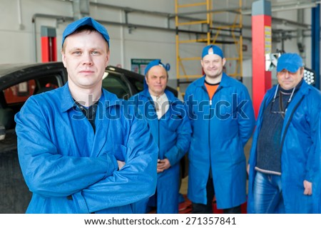 Teamwork: Group of Engineers and Mechanics People in Car Service Workshop - stock photo