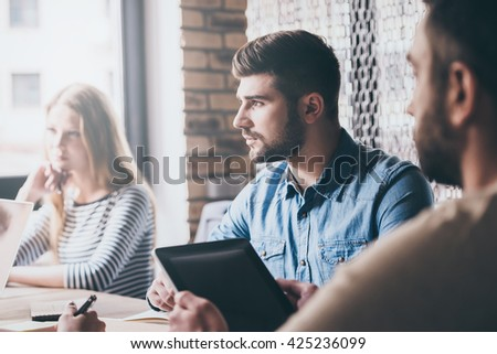Teamwork. Group of young people looking away while sitting at the office table at the business meeting  - stock photo