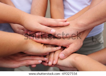 teamwork, group putting hands together - stock photo