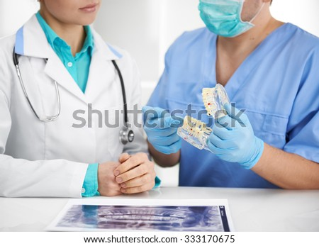 Teamwork in dental clinic. Portrait of two dentists analyzing tooth anatomy with jaw model and teeth X-ray. - stock photo