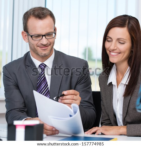 Teamwork in the office with a business man and woman sitting close together at a desk discussing a paper document with smiling faces - stock photo