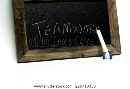 "Teamwork - Miniature construction worker figurines posed as if writing ""Teamwork"" on a chalkboard. - stock photo"