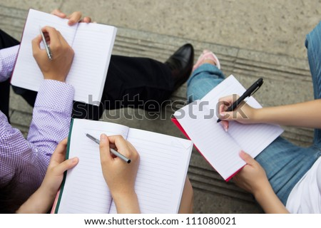 Teamwork of group people holding notebooks. Group of young students holding pen and writing in book - stock photo