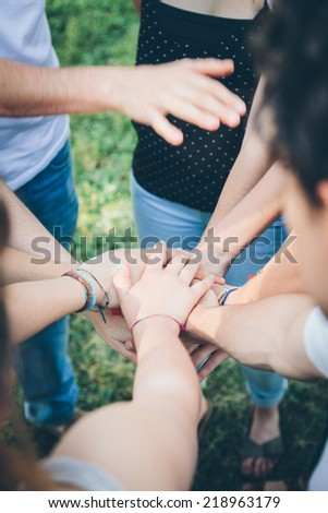 Teamwork, pile of hands of kids to the park - stock photo