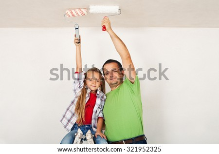 Teamwork - proud father and daughter painting the room ceiling together - stock photo