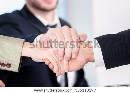 Teamwork. Three successful business people sitting in the office and do business while businessmen shake hands with each other and work at a laptop