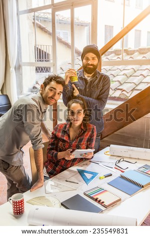 Teamwork. Three young architects working on a project at a table in the study - stock photo