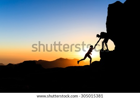 Teamwork trust couple helping hand trust help silhouette in mountains. Team of climbers man and woman help each other on mountain top, inspiration and motivation together, inspirational landscape - stock photo
