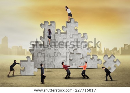 Teamwork try to connect puzzle and solving the problem - stock photo