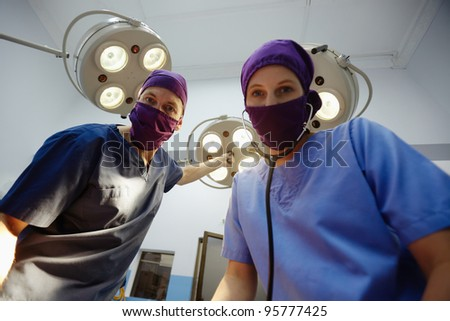 Teamwork with nurse and surgeon performing surgery in hospital operation room - stock photo