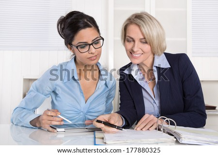 Teamwork with trainee and mature boss at desk. - stock photo