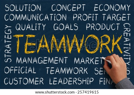 Teamwork word cloud is written on blue chalkboard by the hand of a businessman. - stock photo