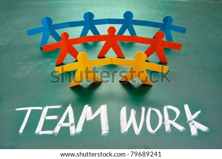 Teamwork words and colorful paper dolls on  blackboard - stock photo