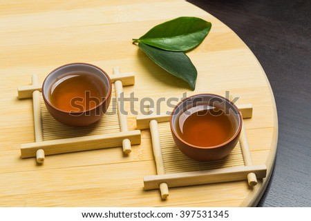 Teapot and a cup of green tea on wooden table - stock photo