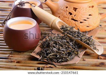 Teapot and aromatic oolong tea leaves on bamboo mat background