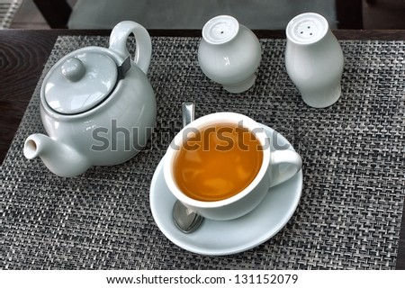 teapot and cap of tea on table - stock photo