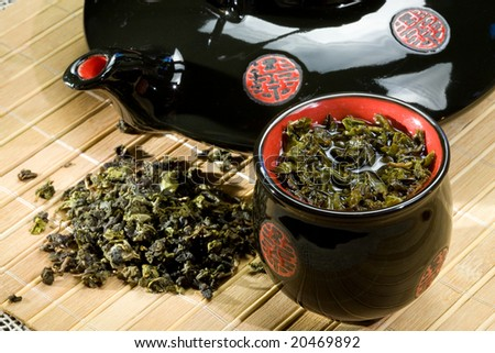 Teapot and cup filled by green tea - stock photo