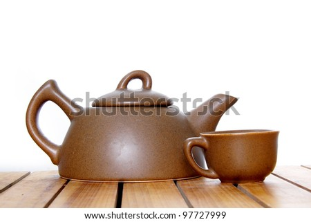 teapot and cup on wooden table over white - stock photo