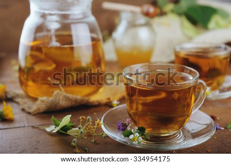 Teapot and cups of herbal tea with linden flowers and strawberries on wooden table - stock photo