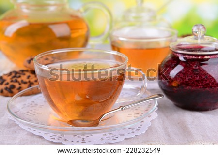 Teapot and cups of tea on table on bright background - stock photo