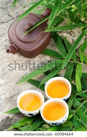 Teapot and cups on stone with bamboo leaves. - stock photo