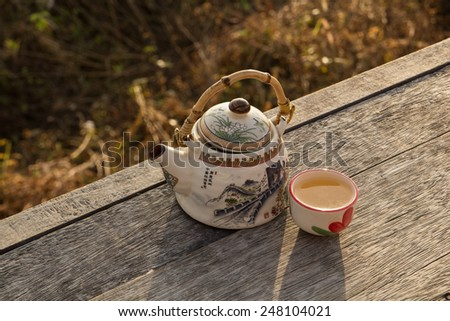 Teapot and cups on wood table - stock photo