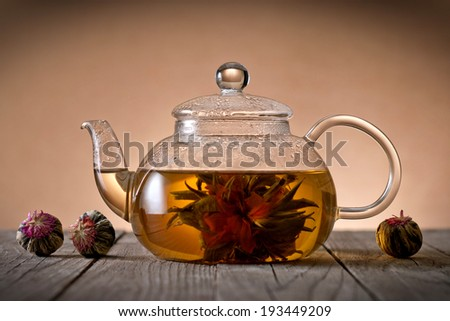 Teapot and glass cup with blooming tea flower - stock photo