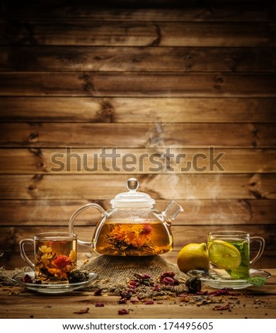Teapot and glass cups with  tea against wooden background  - stock photo