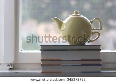 Teapot and pile of old books on rustic window. Selective focus.  - stock photo