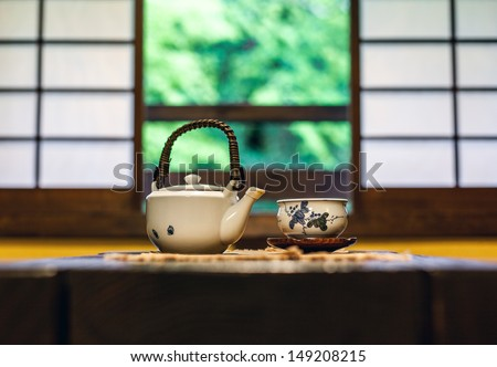 Teapot and tea bowl on a table in a traditional Japanese room in front of Shoji screen windows. Natural light and shallow depth of field. - stock photo