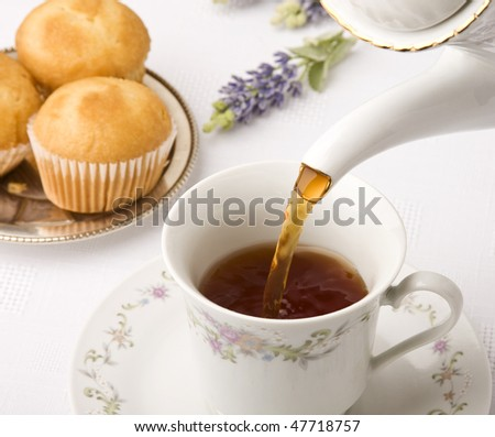 Teapot close up pouring tea into a cup. Focus on pouring. - stock photo