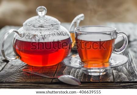 Teapot, cup and hot tea. - stock photo