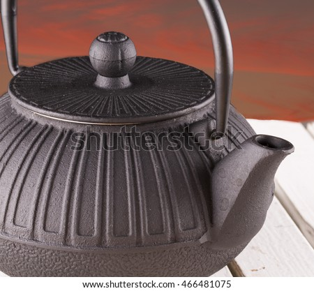 Teapot in close up, with sunset sky on the background