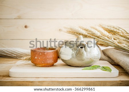 Teapot on wooden and sackcloth background. - stock photo