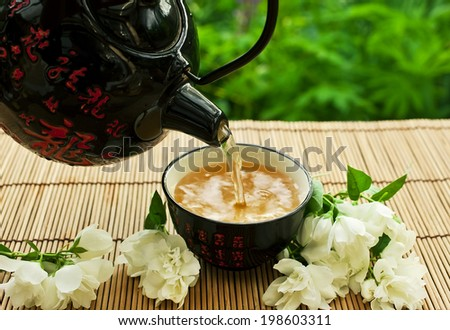 Teapot with bowl of jasmine green tea - stock photo