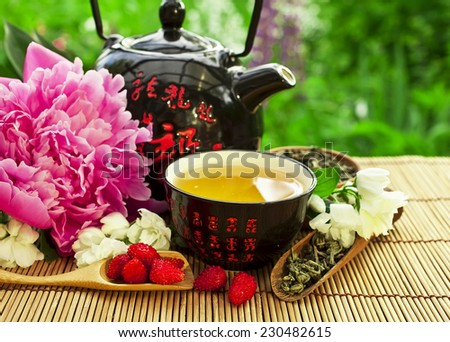 Teapot with bowl of jasmine green tea and peony flower  - stock photo