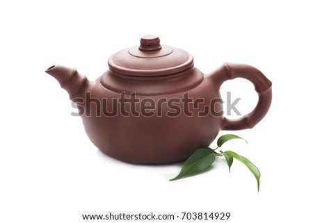 Teapot with green leaves isolated on white background