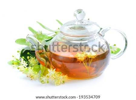 Teapot with linden tea and flowers - stock photo