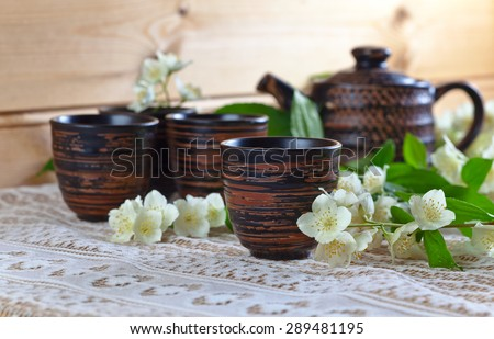 Teapot with small cups and jasmine flowers