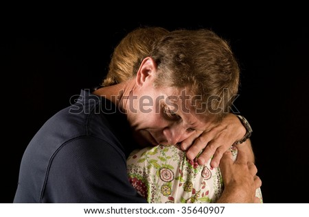 Tearful hug - man and woman have emotional embrace, suggestive of grief, relationship crisis, or reconciliation. - stock photo