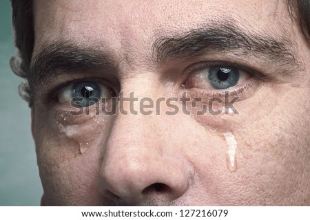 Tears in eyes of crying adult man - stock photo