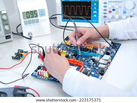 Tech tests electronic equipment in service facility  - stock photo
