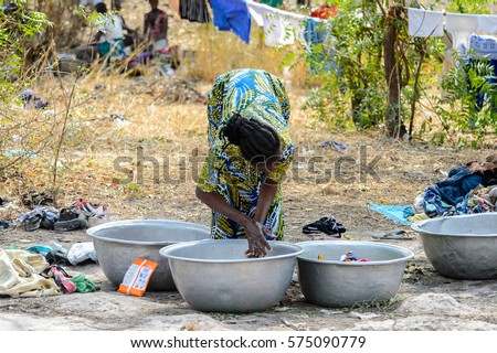 TECHIMAN, GHANA - JAN 15, 2017: Unidentified Ghanaian woman cleans clothes on the Washing Day, which is every Sunday