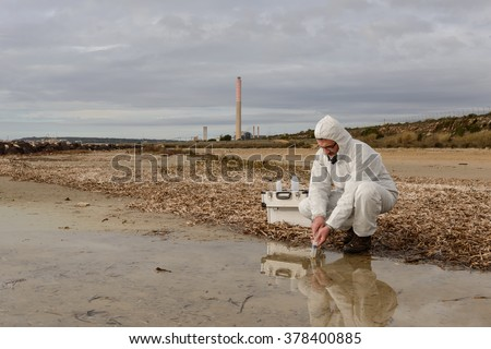 Technical expert, observes the tube containing polluted water. / Polluted Water Analysis. / Industrial district - stock photo