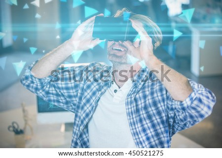 Technical screen with little pyramids against smiling businessman using virtual reality simulator - stock photo