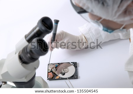 Technical surgeon working on hard drive - data recovery - stock photo